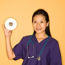 Asian Chinese mid-adult female doctor holding holding up CD against yellow background smiling and looking at viewer.