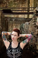 Sexy tattooed Caucasian woman standing next to concrete wall.