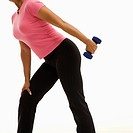 Side view of mid adult multiethnic woman wearing pink shirt exercising with dumbbell.
