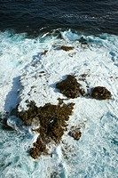 Aerial view of rocks in Pacific ocean with water swirling around them off the coast of Maui, Hawaii