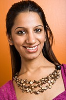 Attractive young adult Indian woman smiling at viewer.