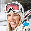 Attractive young blond woman in winter ski gear smiling.