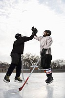 Two boys in ice hockey uniforms giving each other high five on ice rink