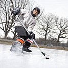 Boy in ice hockey uniform skating on ice rink moving puck