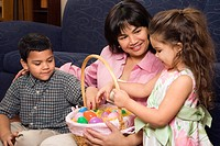 Hispanic mother with her boy and girl at home looking through Easter basket.