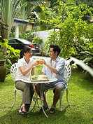 man and woman having breakfast in their garden