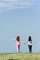 Two young women walking hand in hand outdoors, rear view