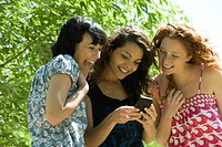 Three young women outdoors, looking at smartphone together