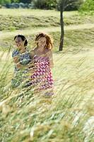 Two young women laughing together outdoors, tall grass in foreground