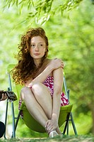Young woman sitting in folding chair outdoors, looking away