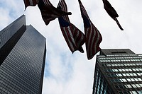 Skyscrapers, flags waiving in breeze, viewed from below