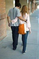 Young couple walking with arms around each other's waists, rear view