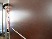 Female office worker peering behind wall