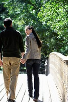 Couple walking on footbridge rear view