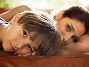 Mother and son lying on sofa
