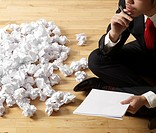 Businessman Thinking beside Crumpled Paper