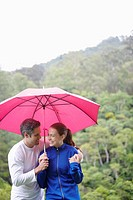 Couple with umbrella walking near forest