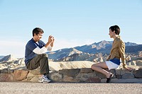 Man photographing woman on stone wall in desert, Death Valley, California, USA