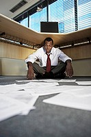 Mid Adult Man Doing Paperwork Under Desk
