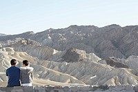 Couple sitting on stone wall in desert rear view, Death Valley, California, USA