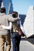 Couple walking with arms around each other rear view