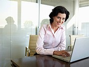 Young businesswoman using laptop computer portrait