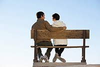 Young couple sitting on bench rear view