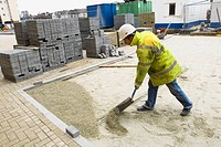Laying recycled glass material for paving stone. England, UK