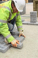 Laying paving stone on base made of recycled glass material. England, UK