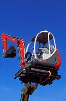 Mini excavator raised on boom of telescopic forklift