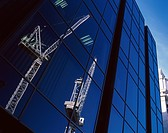 Lattice boom cranes reflected in modern glass facade