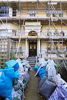 Property under refurbishment with scaffolding and waste in the front garden