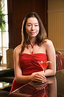 Taiwanese mid adult woman in red dress at bar with a drink.