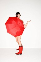 Young sexy Caucasian woman in red boots holding red umbrella and checking for raindrops