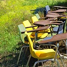 Old school chairs in grassy field (thumbnail)