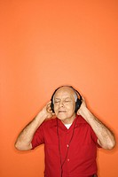 Mature adult Caucasian male listening to headphones.
