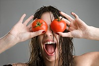 Caucasian woman with tomatoes covering her eyes