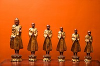 Wooden statues of Buddha with five disciples against orange wall