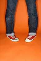 Person in jeans and sneakers with feet turned inward