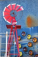 Broken red windmill against rusted blue corrugated metal building covered in taillights