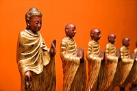 Wooden statues of Buddha with disciples against orange wall