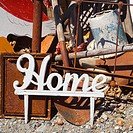 Metal figure with word 'Home' leaning against junk