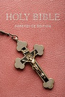 Crucifix lying on cover of closed Holy Bible