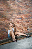 Caucasian mid_adult blonde woman sitting against brick building in alley