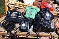 Stack of old broken rotary telephones on table