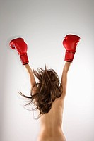 Topless caucasian woman with arms up in the air wearing boxing gloves