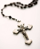 Christian rosary beads with crucifix on white background