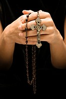 Woman holding rosary with crucifix
