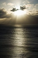 Pacific ocean and island with sun streaming through clouds