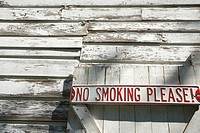 Sign on old white peeling building reading 'No smoking please!'